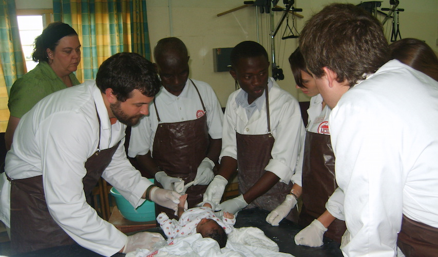 a group of health care students and professionals stand around a newborn on an examining table
