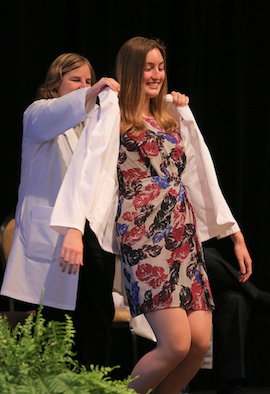 PD Chris Bruce presents white coat to first-year student Emma Lamothe. Photo credit: Darrell Peterson